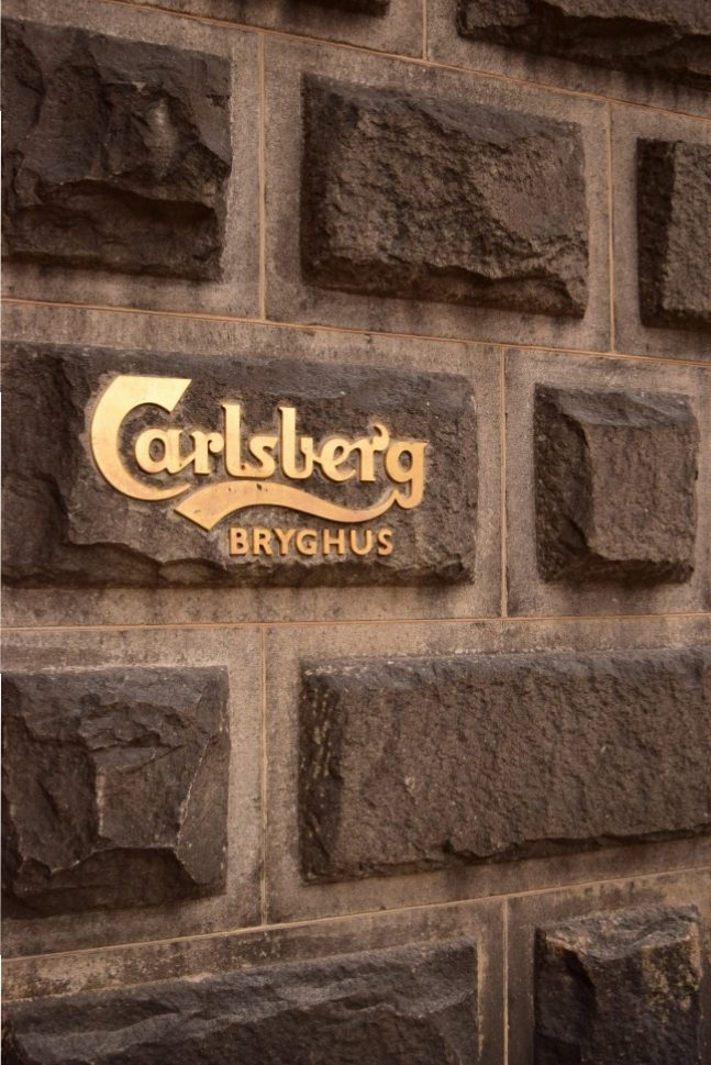 Carlsbergs signature sign on brick wall in gold