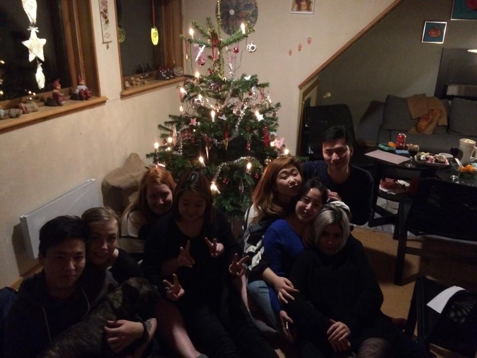 Christmas hygge with friends and family and a dog. Together in front of the christmas tree.