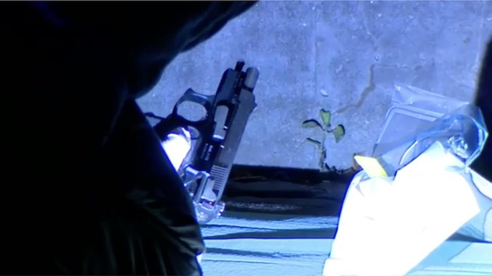 경찰 수사관이 링비 마가신 쇼핑센터 인근에서 권총 1정을 회수하는 모습 (출처: TV2)