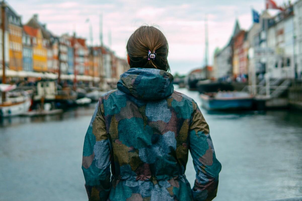 woman beside river between buildings